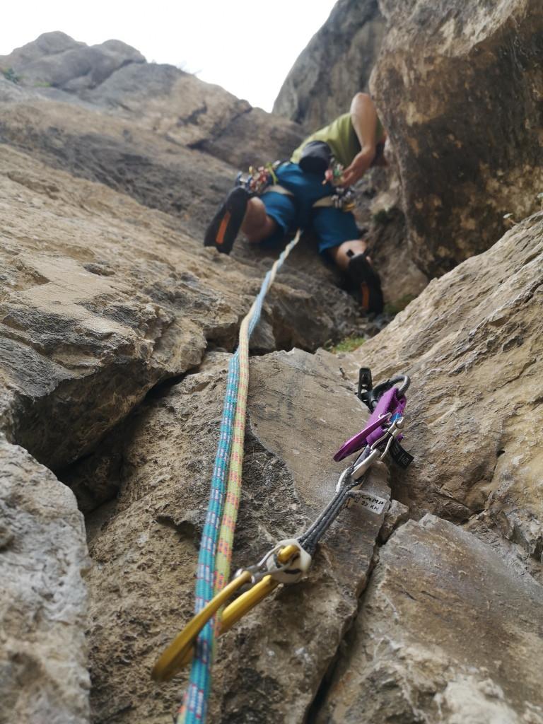 Bergführer klettert über eine mobile Sicherung