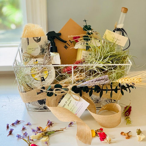 Photo of spa items in the basket - body wash, loofah, salt in a test tube, cream - all with flowers around