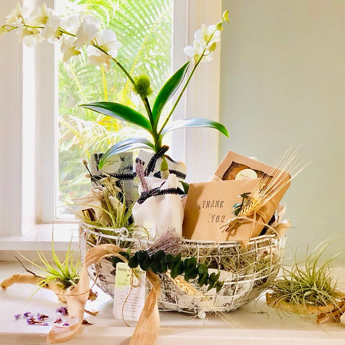 Large basket by a window with an orchid, chocolate bar, caramel sauce, coconut macaroons and items in basket wrapped up.