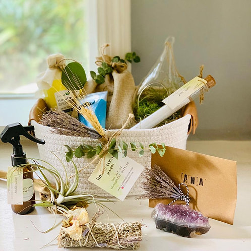 Photo of amethyst, spray bottle, bath salt in glass tube, air plant in rope coil basket by window