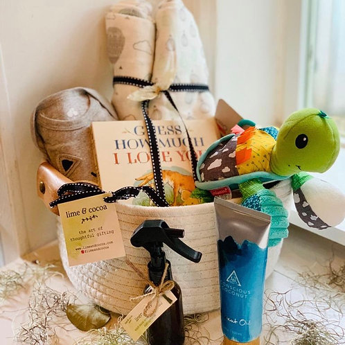 Photo of white basket with leather trim by window with baby book, muslim blanket, hand sanitizer, body oil and baby toy