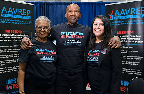 Three people standing with black shirts reading outlives matter our votes count