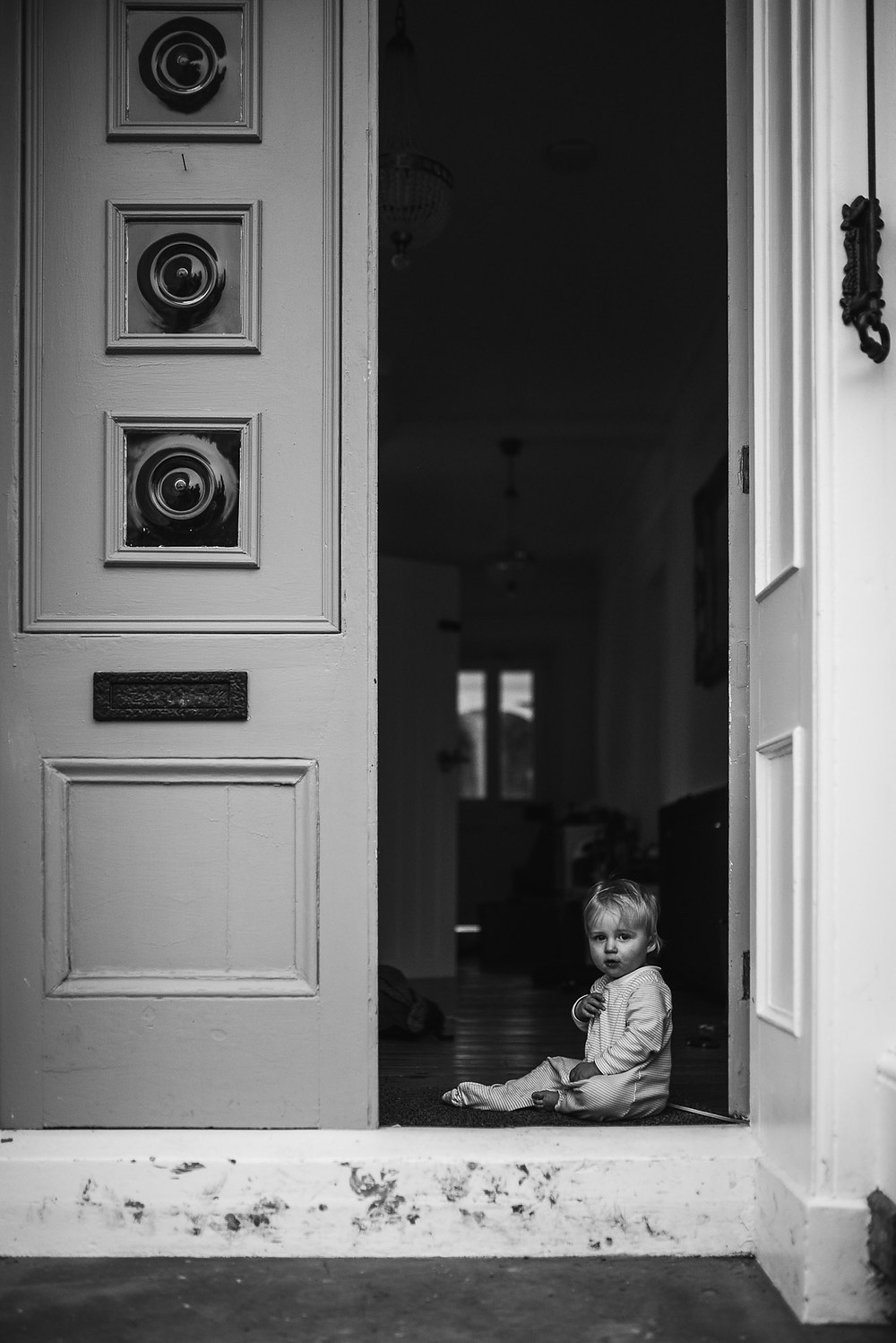 baby sitting inside his front door on a muddy doorstep in black & white