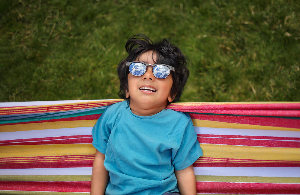 boy in colourful rainbow hammock with sky reflecting in sunglasses