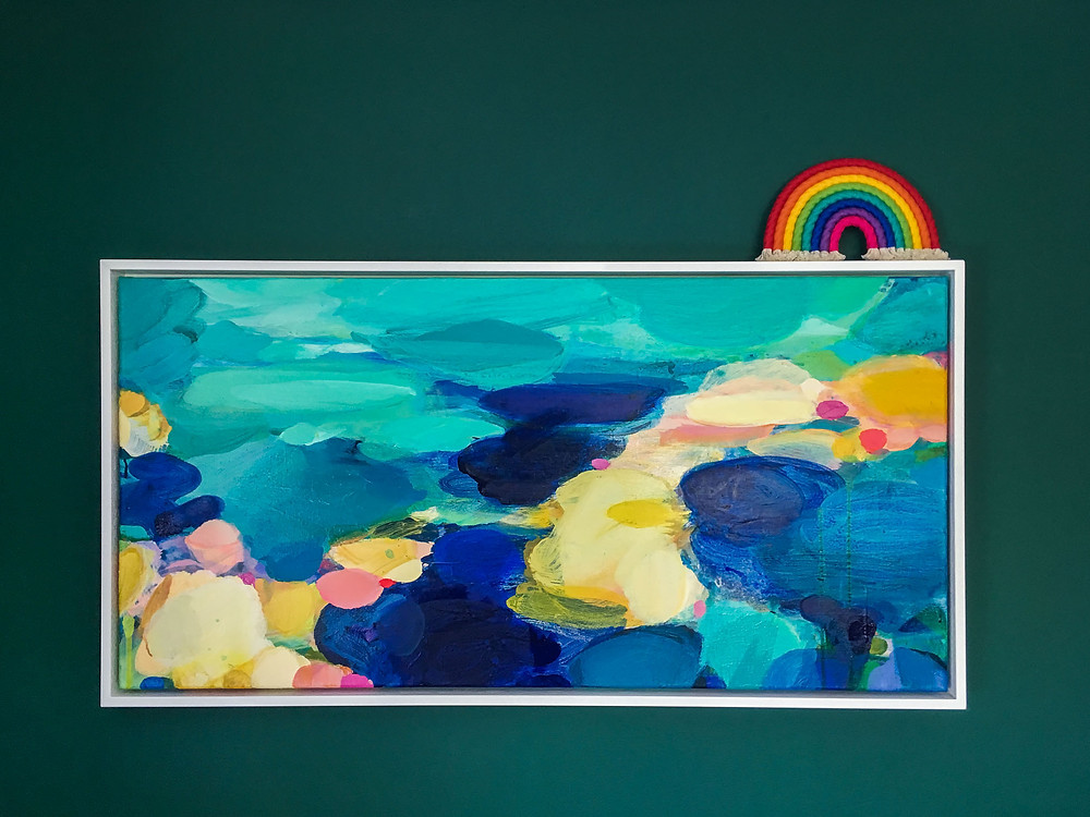 rainbow wrap wall hanging on top of a colourful painting on a dark green wall