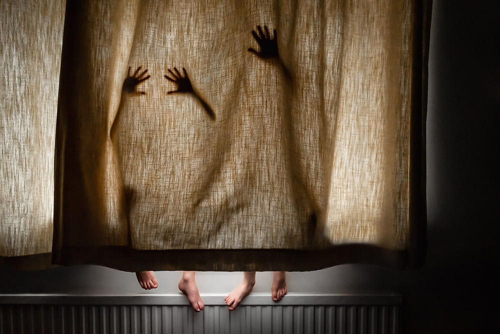 Kids hiding behind curtain with hands, feet and shadows