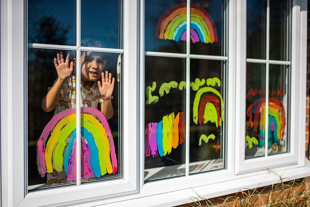 Young boy painting rainbows on his window