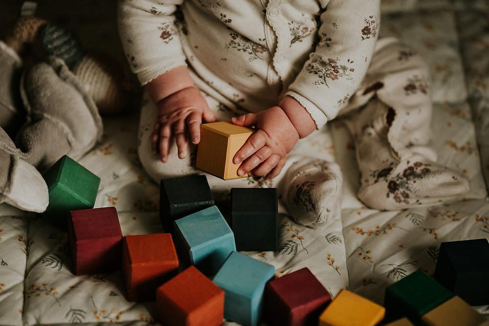 baby hands holding blocks