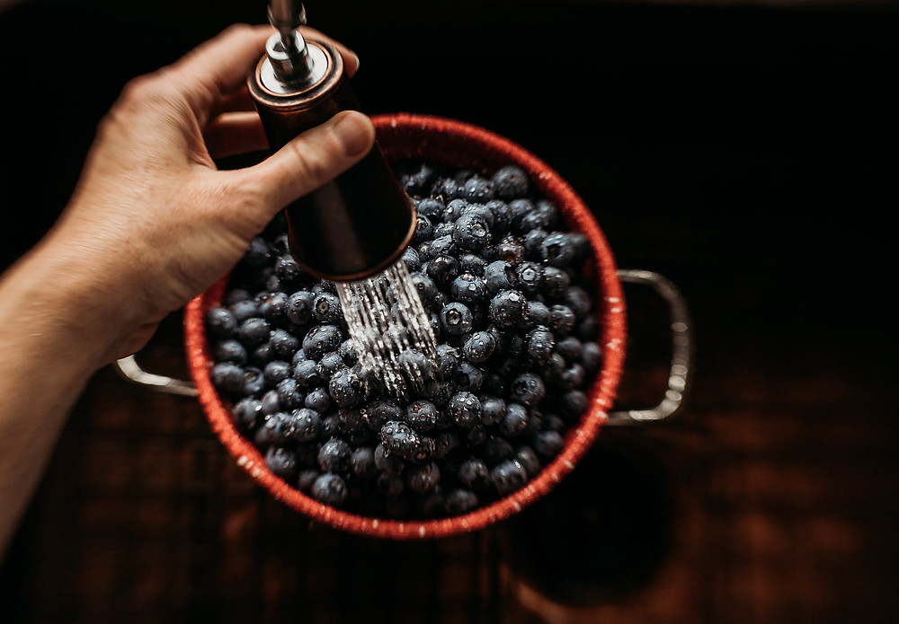 Blueberries being washed in red colander