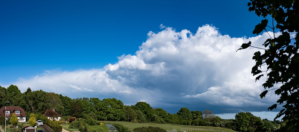 blue skies and huge clouds over countryside homes in Uckfield, East Sussex