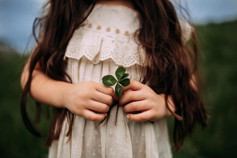 girl holding a four leaf clover