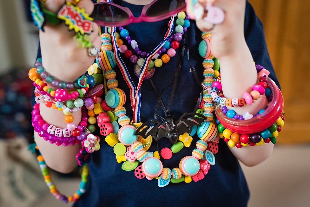 Lots and lots of beaded colourful jewellery on a child