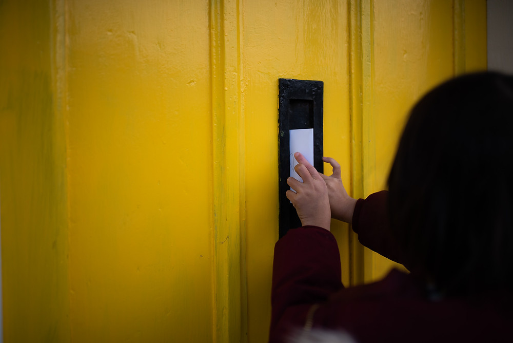 Posting a card through a bright yellow door.