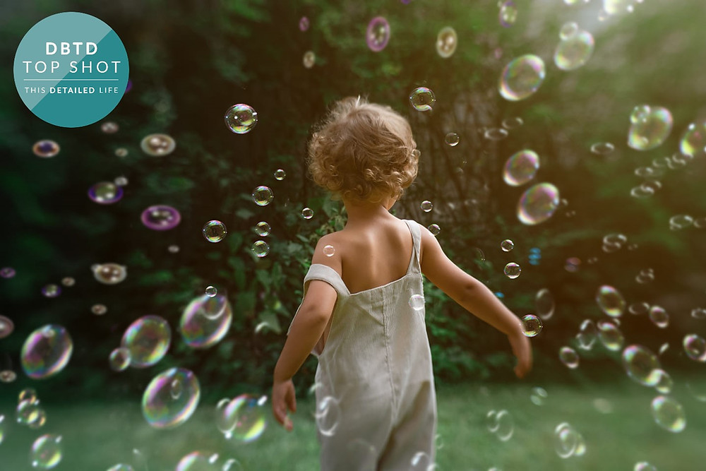 toddler in dungarees surrounded by bubbles