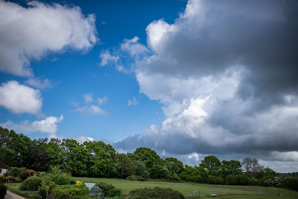 retreating storm clouds and blue skies over countryside in buxted