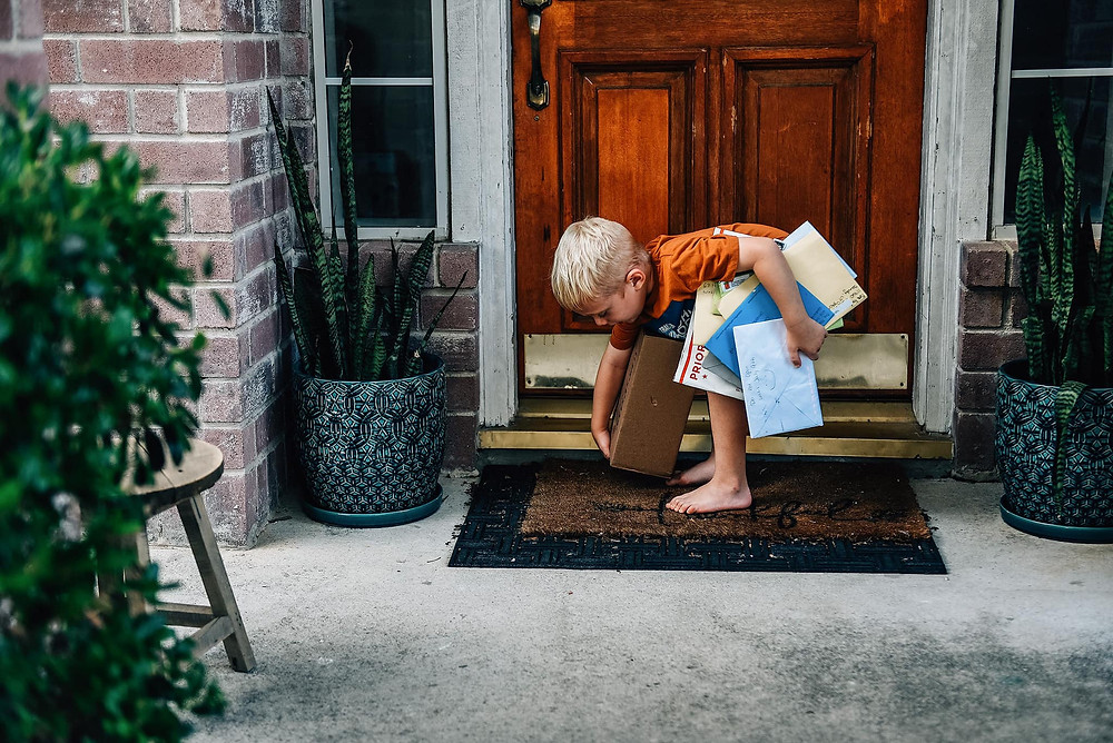 Boy picking up mail and gifts