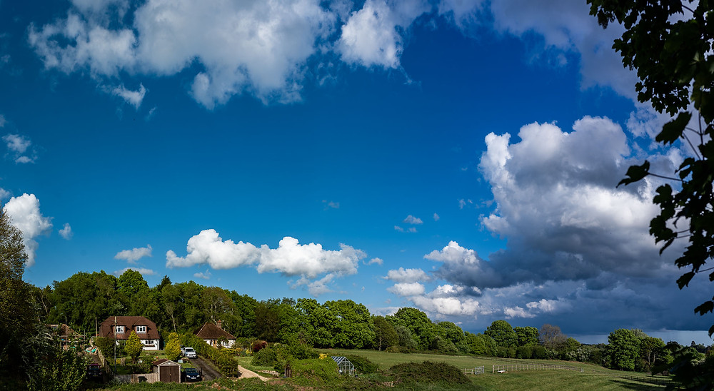 Blue sky and fluffy white clouds over green countryside in Uckfield, East Sussex