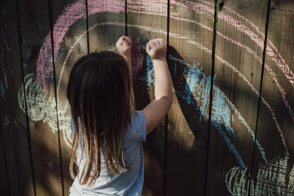 child drawing chalk rainbow on fence