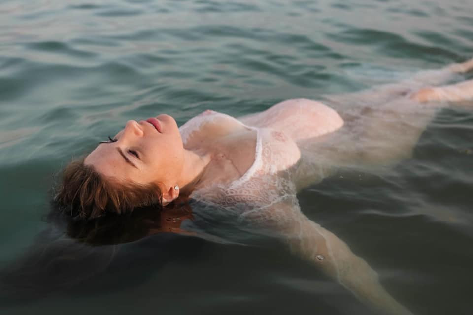 Maternity pregnant woman floating in water in see-through lace dress