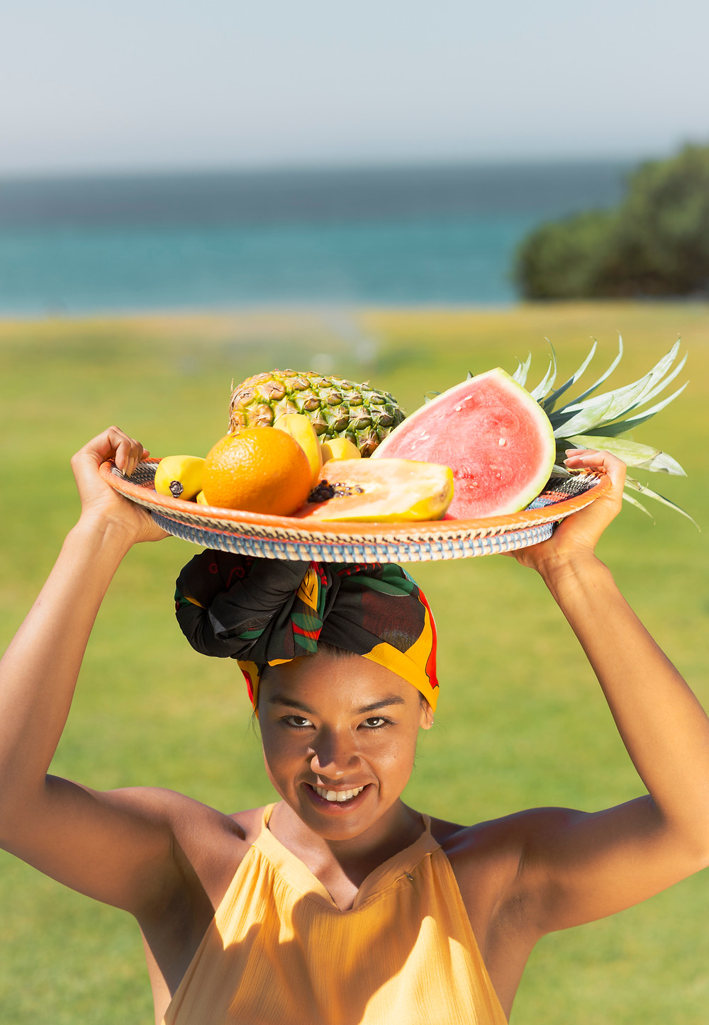 The model holding a tray full of tropical fruit.