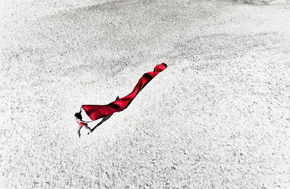 Aerial photography of a woman running with a red fabric-