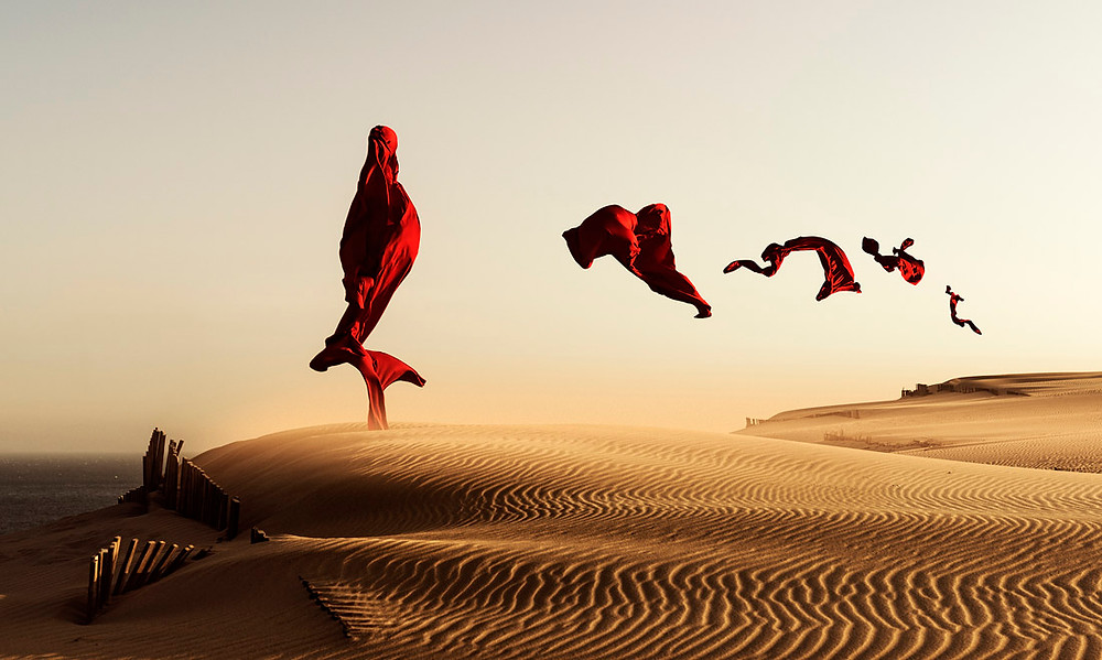 Fine art photography. This image was created on a very windy day so the red cloth would fly and form different shapes. The sand dunes of Punta Paloma, Tarifa, Costa de la Luz, Andalusia, Spain.