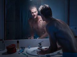 El hombre reflejado en el espejo.