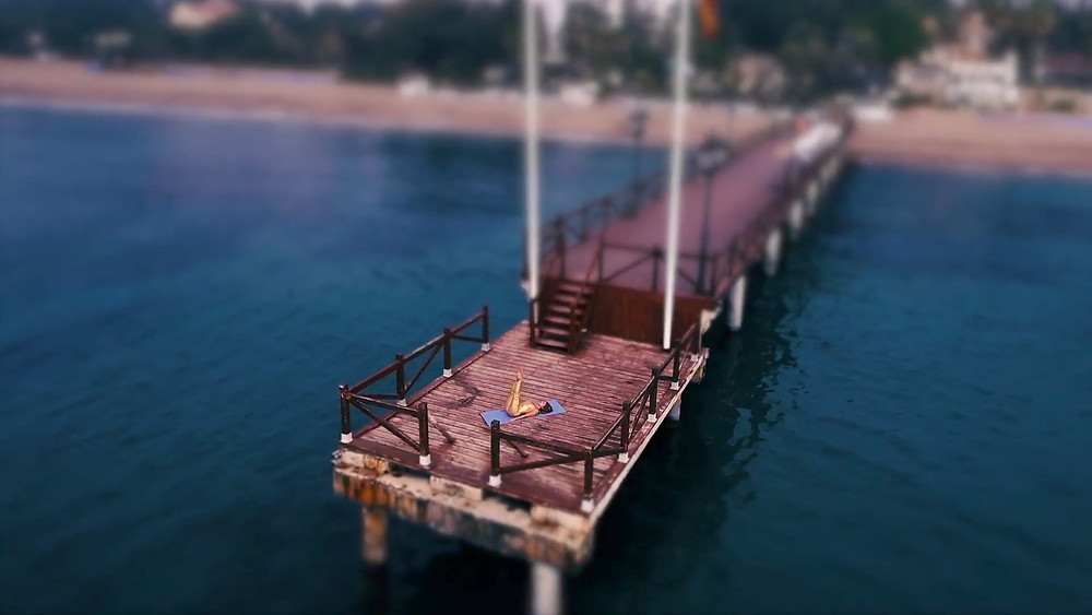 Aerial photography from a drone of Ana doing pilates at the pier on the beach next to Marbella Club. She loves to come here early in the morning to breath and feel the swell of the mediterranean sea.