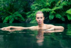 Joven mujer en un estanque natural.