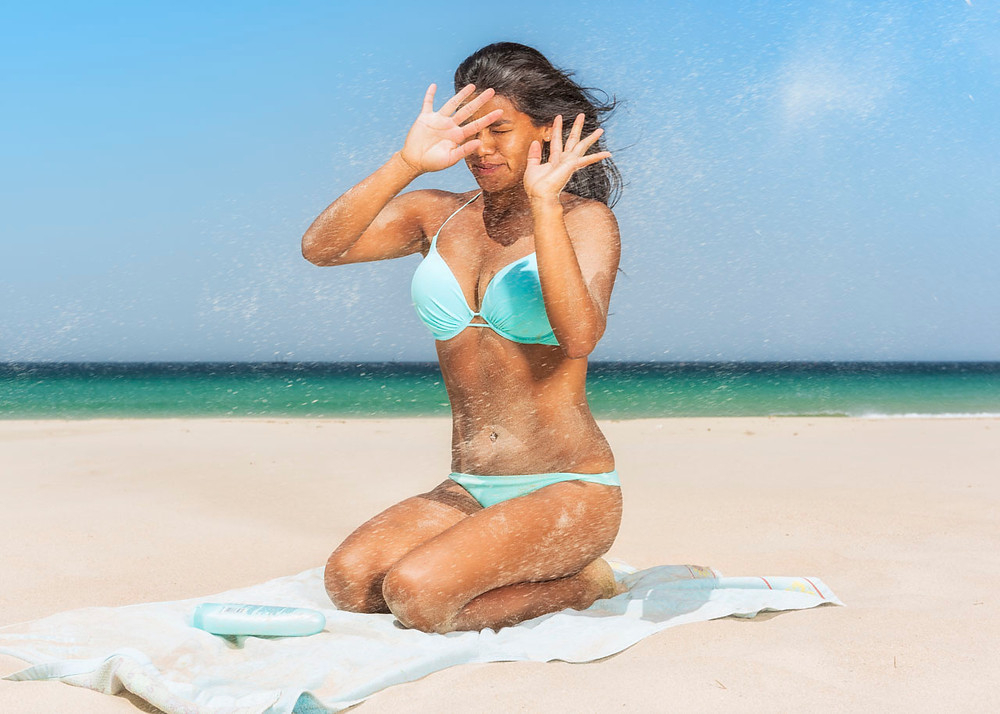 Woman getting sand in her face.