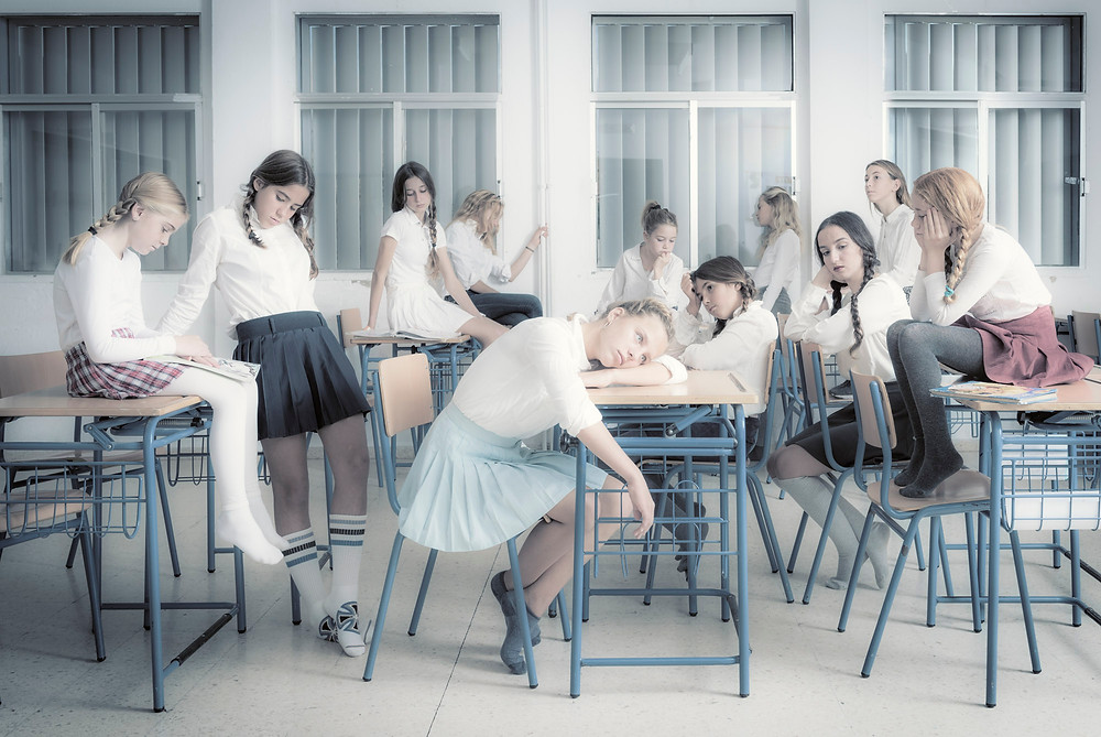 Bored students in a classroom. Photographer Ben Welsh wanted to show the feeling young kids sometimes have when the lessons get to long. This image is part of a series about the human being and the relationship they have when they are together in a group.