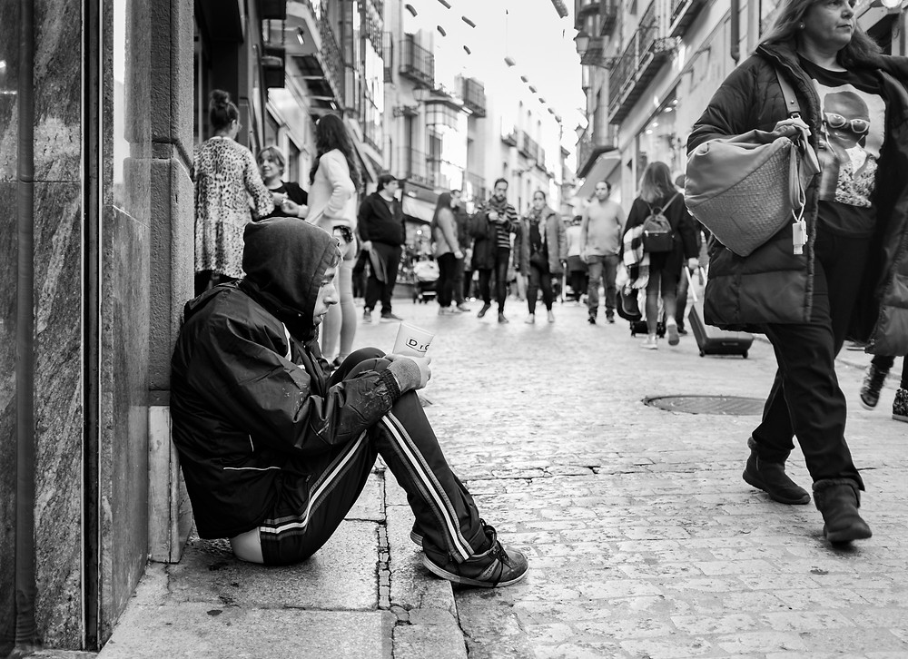 A young man begging on the street.