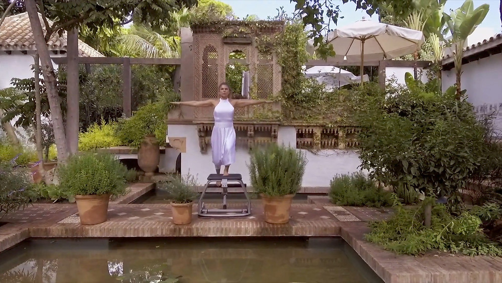 Ana Duran practising on a pilates chair in one of the many beautiful gardens at the Marbella Club.