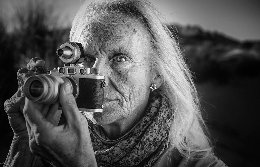 Portrait of a senior woman photographer holding a vintage Leica. This camera was from Ben´s Grandfather and was passed on to his father who is also a photographer.