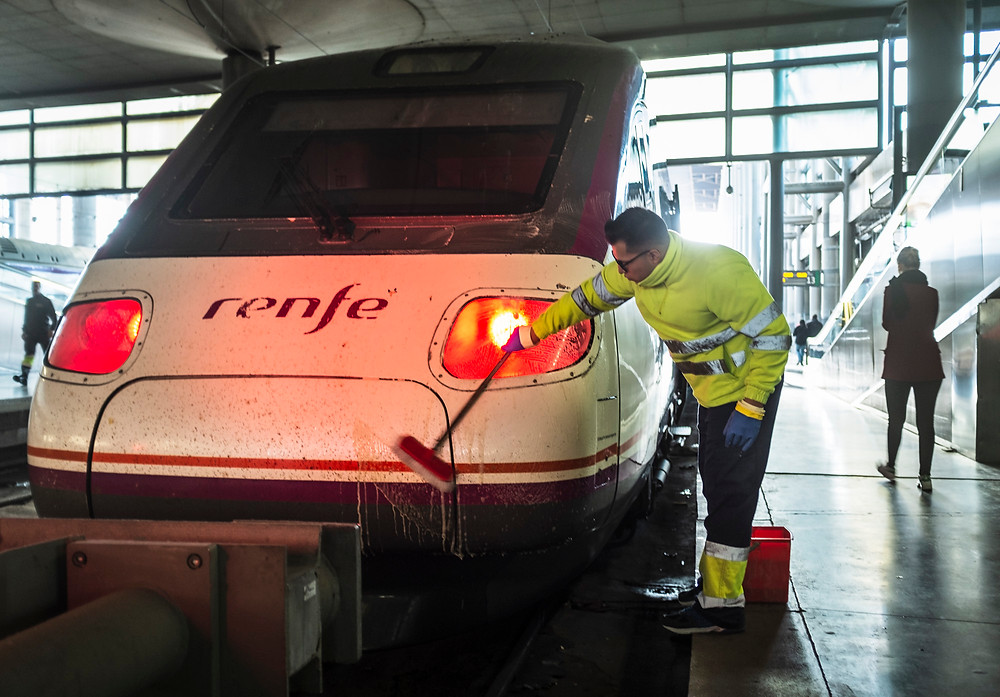 A employee cleaning the front part of a train.