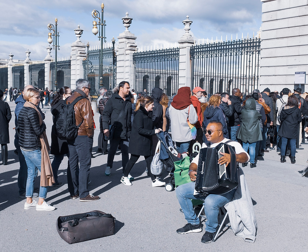 A musician entertaining tourists in a cue.