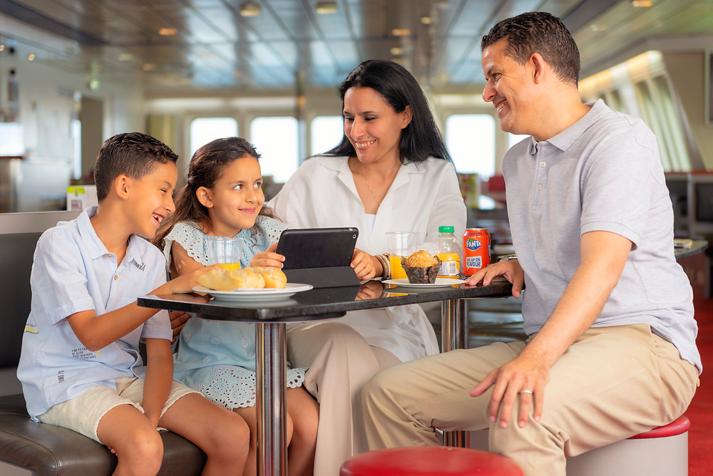 Happy moroccan family in the restaurant of the ferry.