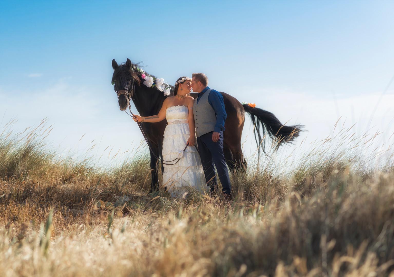 Pareja de recién casados junto a un caballo.
