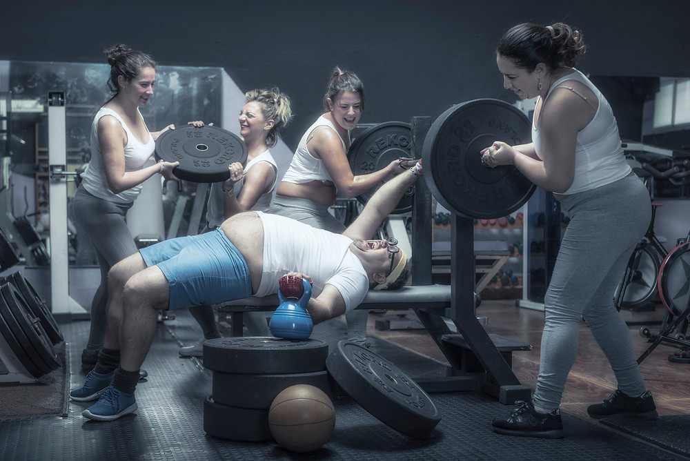 Women helping a man to get fit.