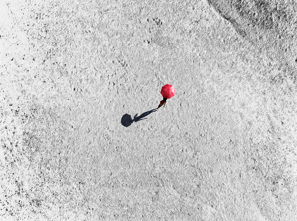 A lonely red umbrella photographed from a drone.