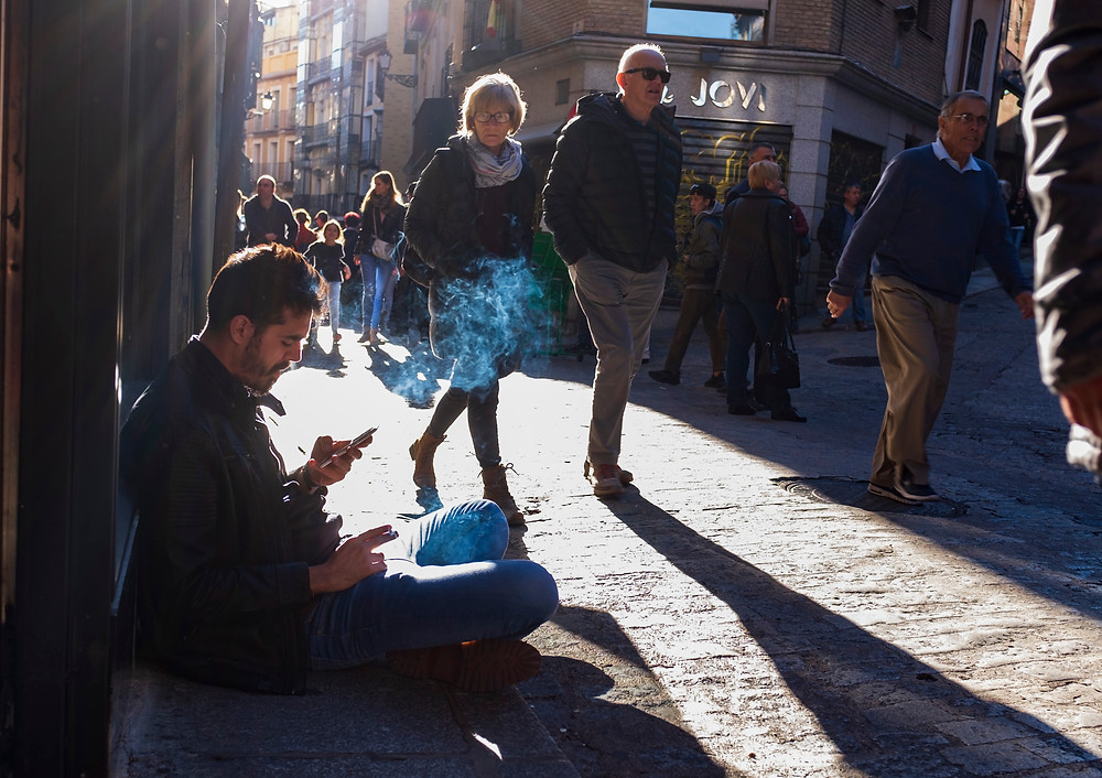 A woman looking at a man sitting on the street pavement.