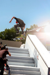 Frontside kickflip skateboard trick down the stairs at a contest.  Invisiblesmiley (c)2020