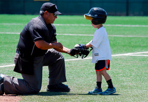 A bat boy hands off some baseballs to the umpire.  Invisiblesmiley (c)2020