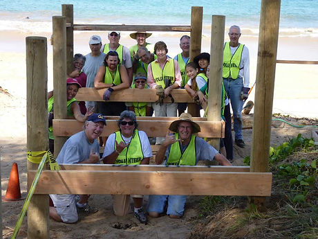 Group of South Maui Volunteers posed around the early construction of a dune walkover