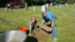 Two volunteers repair cemetery tombstones