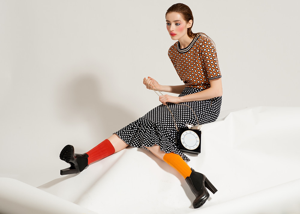 Fashion model sitting on floor with clock purse vintage outfit