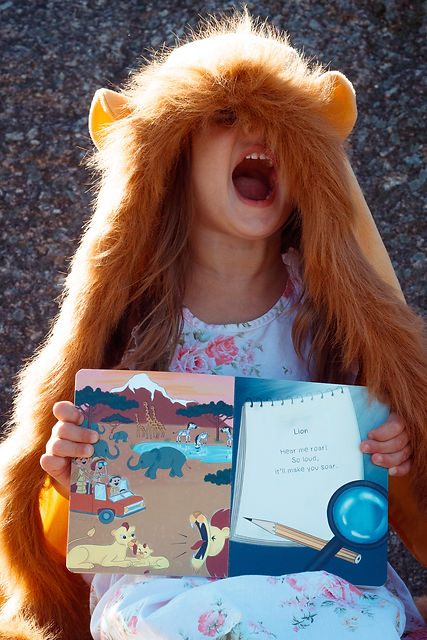 Toddler reading a kid's picture book with animal riddles for kids while acting and roaring like a lion