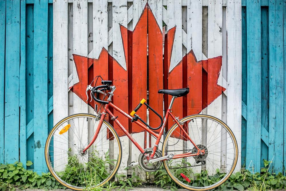 Kanada Flagge an eine Mauer gemalt, davor ein Rennrad. Express Entry
