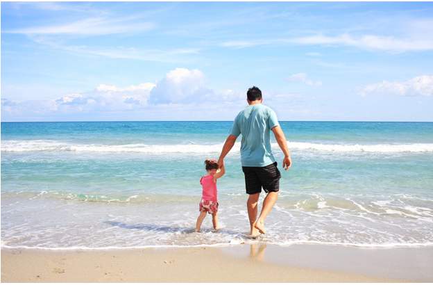 Man on beach with child photo credit Pixabay