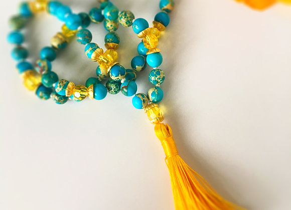 An Aroha Soul wrist mala made with turquoise beads and yellow Swarovski crystals.